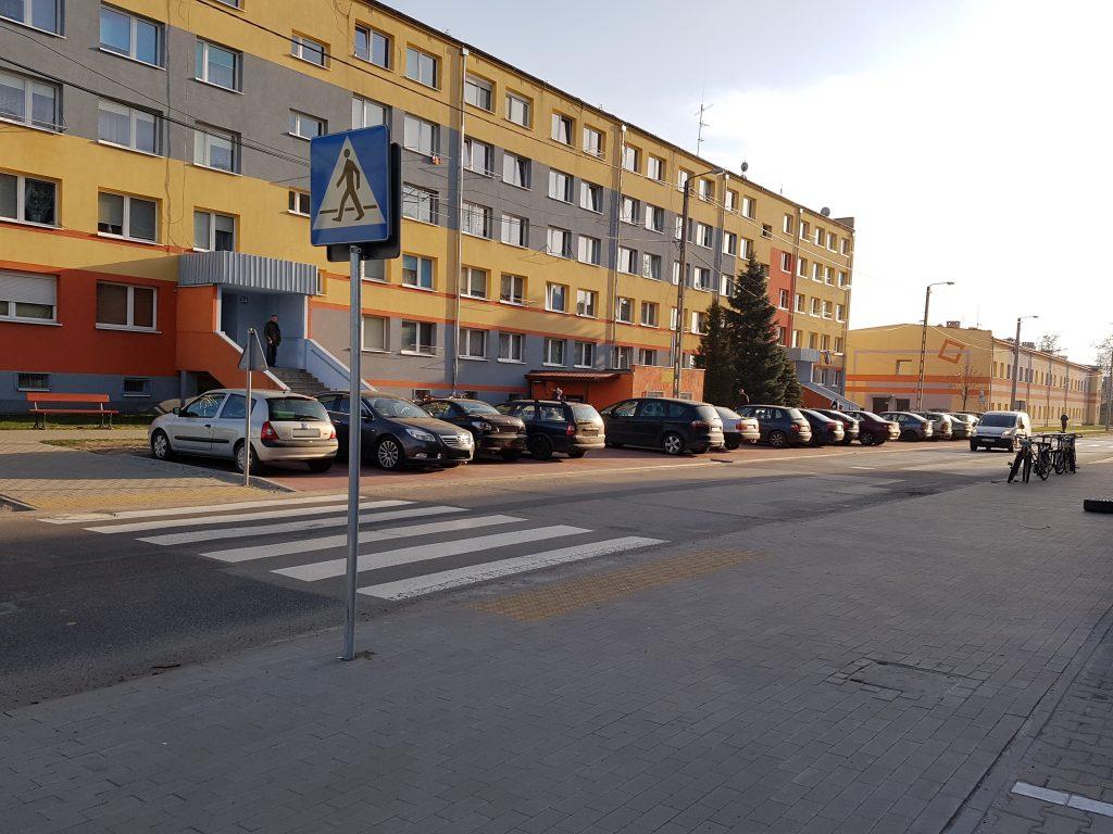 zdjęcie przedstawia uporządkowaną przestyrzeń publiczną - chodniki, ciąg pieszo-rowerowy, parking