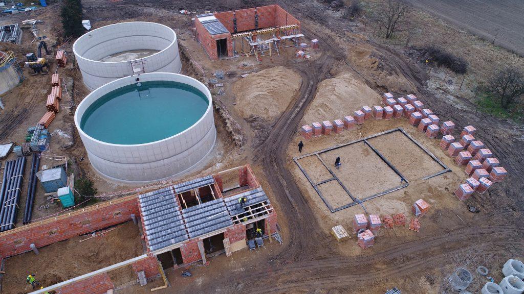 Zdjęcie przedstawia proces budowlany podczas rozbudowy oczyszczalni ścieków, na pierwszym planie fundamenty i sciany nosne budynku, na drugim planie osadniki na ścieki zasobniki na ścieki,