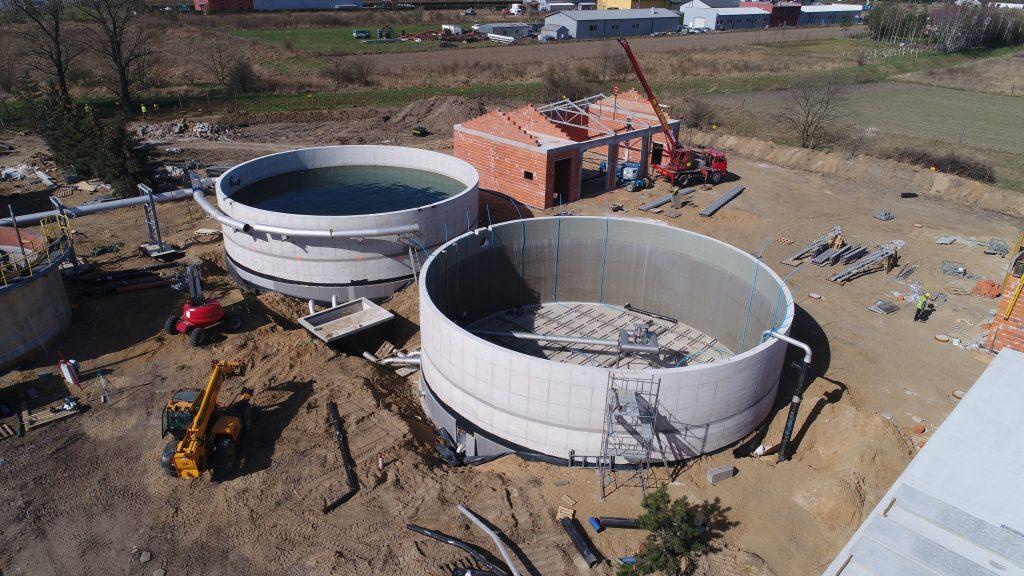 zdjecie przedstawia proces budowlany oczyszczalni ścieków - na pierwszym planie budowa zasobników na ścieki, dalej budynek w budowie