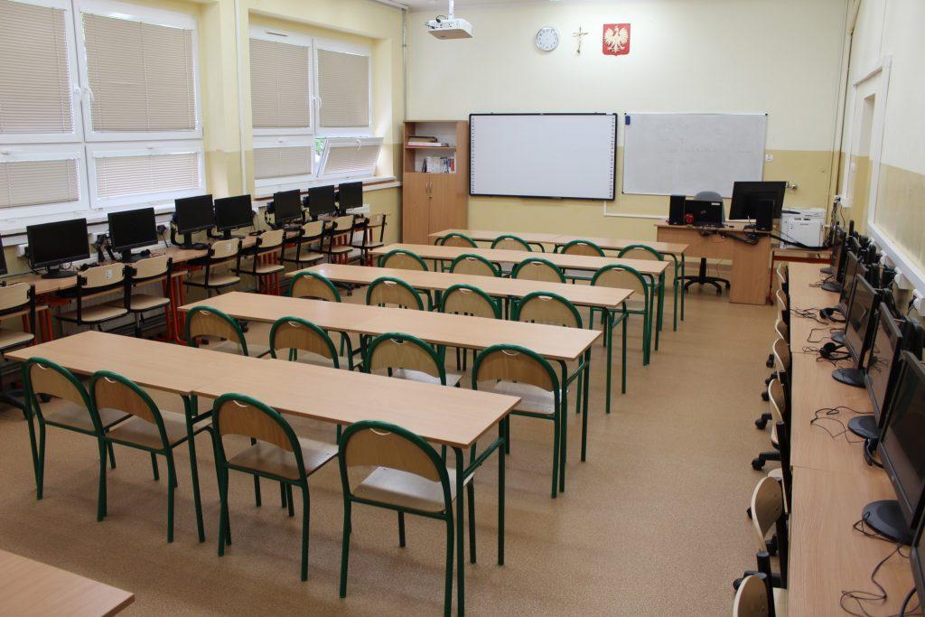 zdjęcie przedstawia gabinet wyposarzony w komputery i tablicę multimedialną