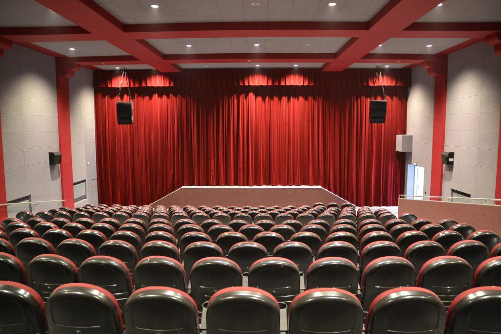 zdjecie przedstawia salę kinową w Gminnym Centrum Kultury w Trzebnicy, na pierwszym planie rzędy krzeseł dla widowni, w tle scena i czerwona kurtyna